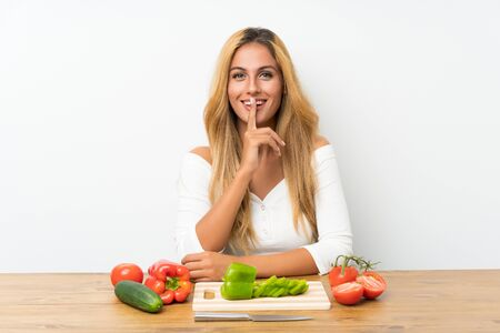 Young blonde woman with vegetables in a table doing silence gesture