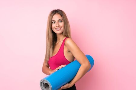 Young sport blonde woman over isolated pink background with a mat and smiling