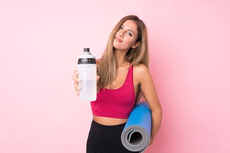 Young sport blonde woman over isolated pink background with sports water bottle and with a mat Stock Photo