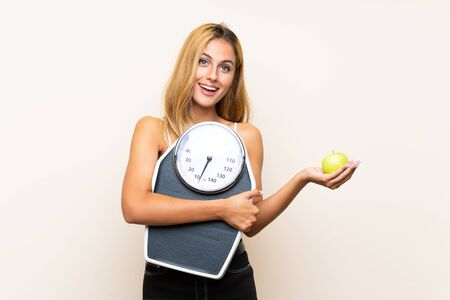 Young blonde woman with weighing machine and with an apple over isolated background