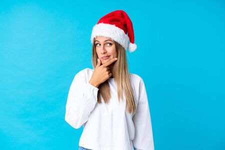 Girl with christmas hat over isolated background thinking an idea Reklamní fotografie
