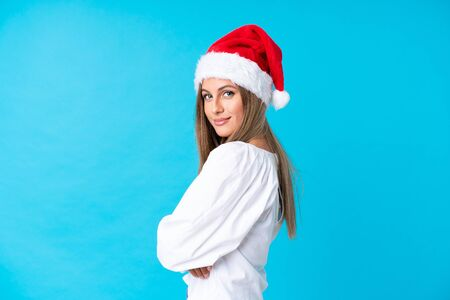 Girl with christmas hat over isolated background laughing