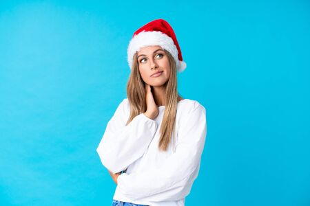 Girl with christmas hat over isolated background thinking an idea