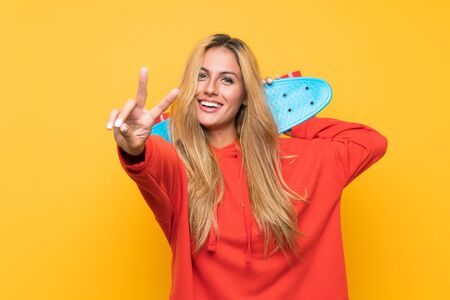 Young skater woman making victory gesture over isolated yellow background