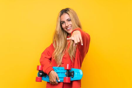 Young skater woman pointing to the front over isolated yellow background
