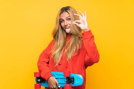 Young skater woman making OK sign over isolated yellow background Stock Photo