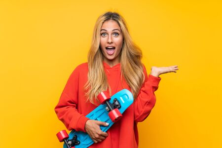 Young skater woman doing surprise gesture over isolated yellow background