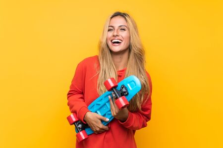 Young skater woman over isolated yellow background Stock Photo