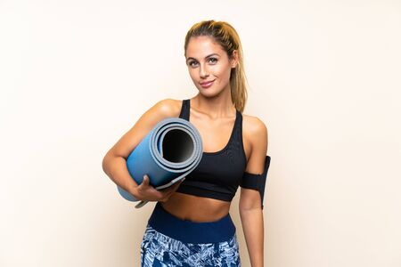 Young sport woman with mat over isolated background