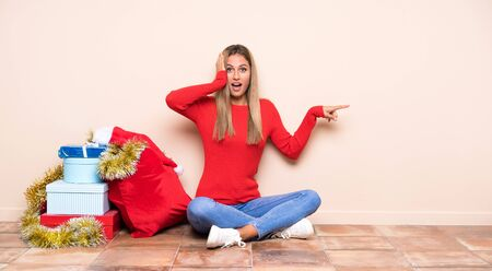 Girl in christmas holidays sitting on the floor surprised and pointing finger to the side