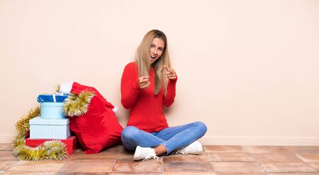 Girl in christmas holidays sitting on the floor points finger at you Stock Photo
