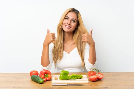 Young blonde woman with vegetables in a table giving a thumbs up gesture