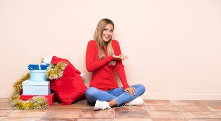 Girl in christmas holidays sitting on the floor extending hands to the side for inviting to come