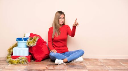 Girl in christmas holidays sitting on the floor touching on transparent screen Stock Photo