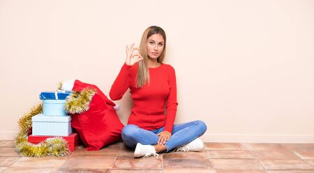 Girl in christmas holidays sitting on the floor showing an ok sign with fingers Stock Photo