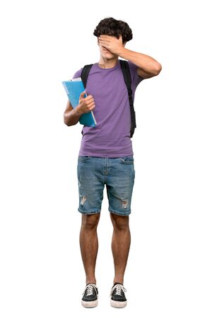 A full-length shot of a Young student man covering eyes by hands. Do not want to see something over isolated white background