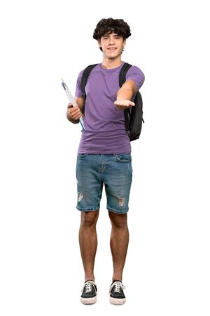 A full-length shot of a Young student man holding copyspace imaginary on the palm to insert an ad over isolated white background
