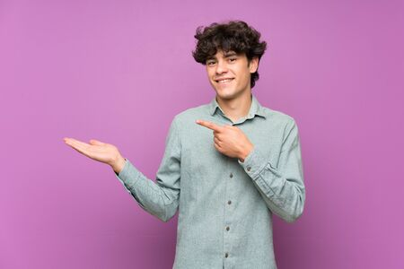 Young man over isolated purple wall holding copyspace imaginary on the palm to insert an ad