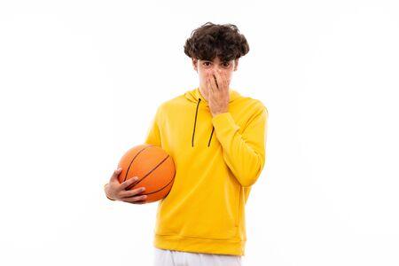 Hombre joven jugador de baloncesto sobre pared blanca aislada con expresión facial sorpresa