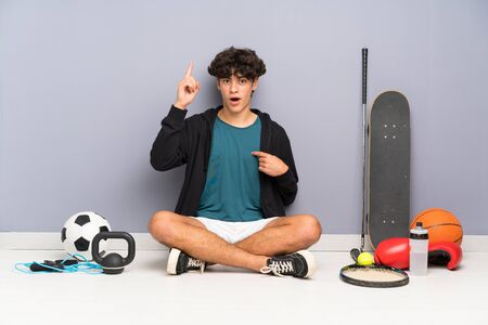 Young sport man sitting on the floor around many sport elements with surprise facial expression