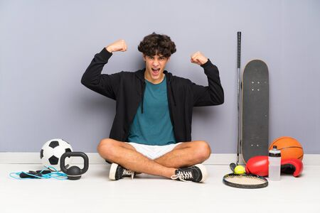 Young sport man sitting on the floor around many sport elements celebrating a victory Stock Photo