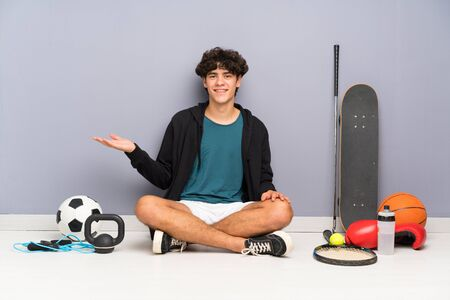 Young sport man sitting on the floor around many sport elements holding copyspace imaginary on the palm