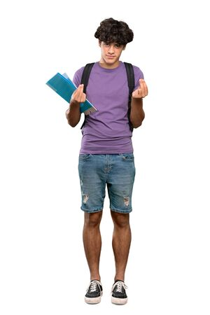 A full-length shot of a Young student man making money gesture over isolated white background