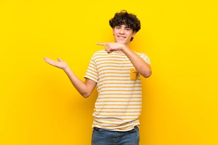 Young man over isolated yellow wall holding copyspace imaginary on the palm to insert an ad Banco de Imagens