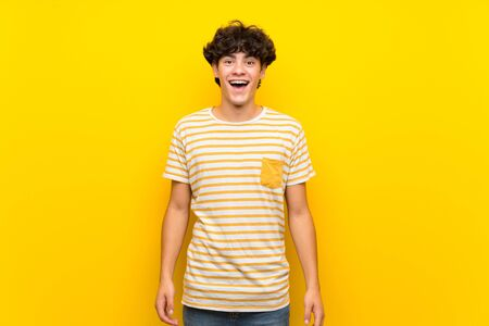 Young man over isolated yellow wall with surprise facial expression Stok Fotoğraf