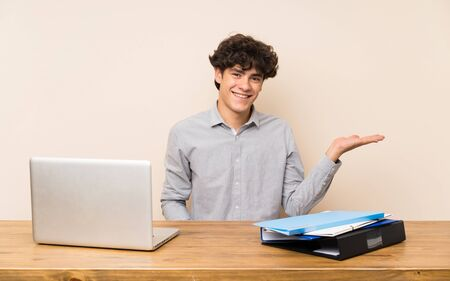 Young student man with a laptop holding copyspace imaginary on the palm to insert an ad