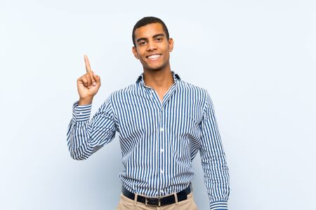 Young handsome brunette man over isolated blue background showing and lifting a finger in sign of the best 版權商用圖片