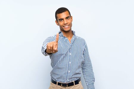 Young handsome brunette man over isolated blue background showing and lifting a finger