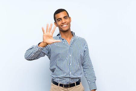 Young handsome brunette man over isolated blue background counting five with fingers