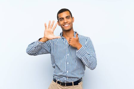 Young handsome brunette man over isolated blue background counting six with fingers 版權商用圖片