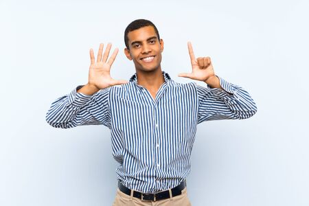 Young handsome brunette man over isolated blue background counting seven with fingers 版權商用圖片