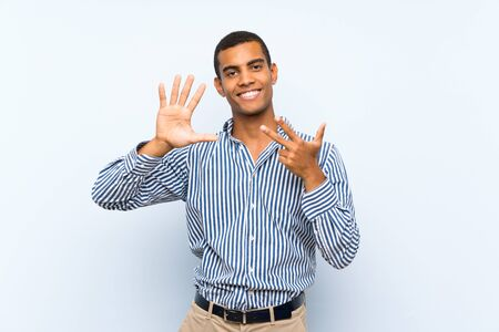 Young handsome brunette man over isolated blue background counting eight with fingers