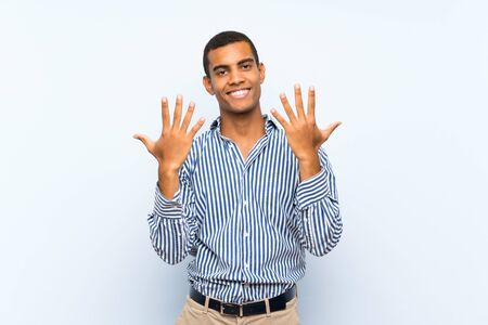 Young handsome brunette man over isolated blue background counting ten with fingers 版權商用圖片