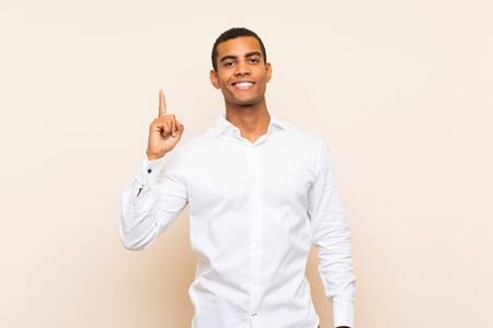 Young handsome brunette man over isolated background showing and lifting a finger in sign of the best 版權商用圖片