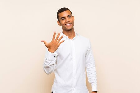 Young handsome brunette man over isolated background counting five with fingers