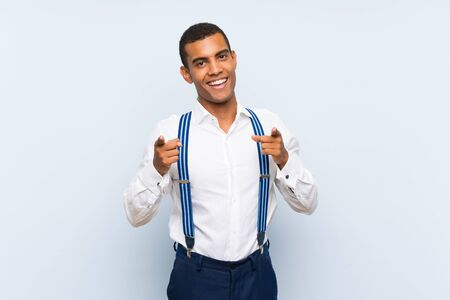 Young handsome brunette man with suspenders over isolated background points finger at you Banque d'images