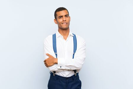 Young handsome brunette man with suspenders over isolated background having doubts and with confuse face expression