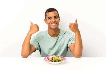 Young handsome man with salad in a table giving a thumbs up gesture