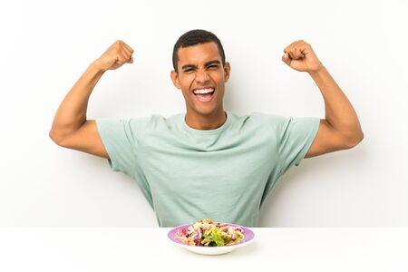 Young handsome man with salad in a table celebrating a victory Banco de Imagens