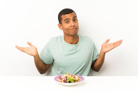 Young handsome man with salad in a table having doubts with confuse face expression