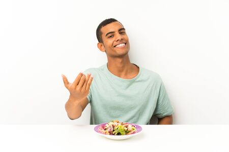 Young handsome man with salad in a table inviting to come