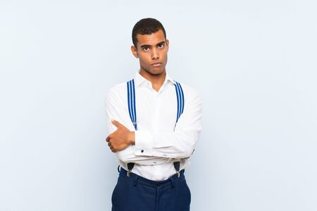 Young handsome brunette man with suspenders over isolated background sad
