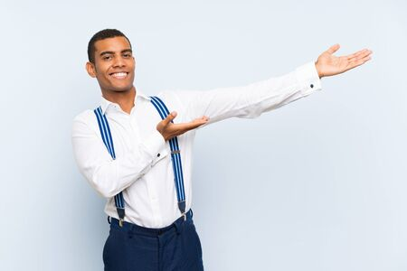 Young handsome brunette man with suspenders over isolated background extending hands to the side for inviting to come