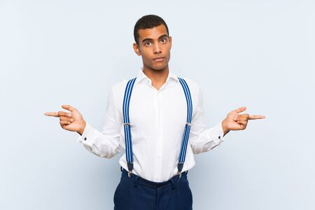 Young handsome brunette man with suspenders over isolated background pointing to the laterals having doubts Banque d'images