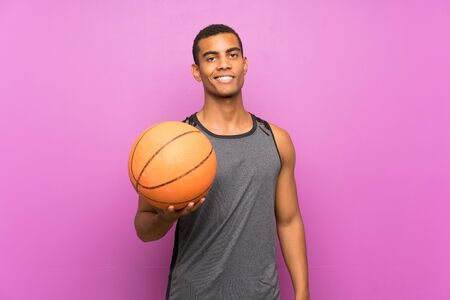 Young sport man with ball of basketball over isolated purple wall smiling a lot Standard-Bild