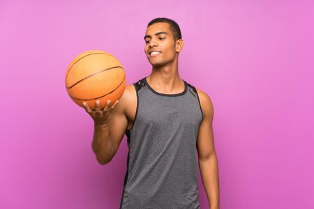Young sport man with ball of basketball over isolated purple wall with happy expression
